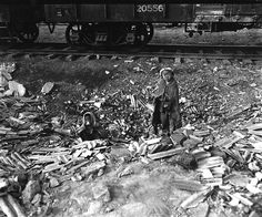 Homeless, this brother and sister search empty cans for morsels of food, and try to keep warm beside a small fire in the Seoul, Korea, railroad yards. November 17, 1950. Pfc. Fulton. (Army)