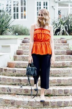 Simple smart outfit with red frill top and black Rebecca Minkoff Moto Tote