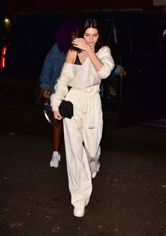 Kendall Jenner in ivory high-waisted parachute pants with a tie-belt, a slouchy ivory sweater and a black clutch while out in Soho.