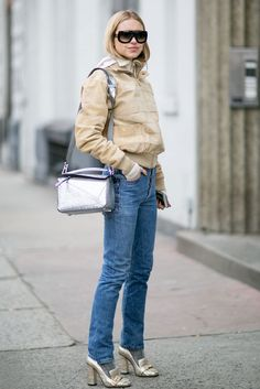 A bomber jacket paired with straight jeans and metallic heels and purse.