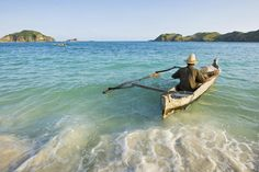 Fisherman paddling his boat out from Kuta Beach.