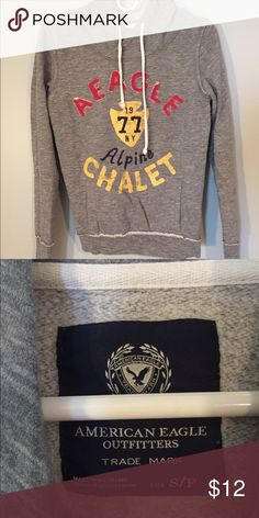 American Eagle Hooded Sweatshirt This hooded sweatshirt has a front pocket and is heathered grey in color. It has an appliqué on the front with embroidery and screen print embellishments. American Eagle Outfitters Tops Sweatshirts & Hoodies