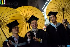 CHINA, HONG KONG : College students in graduation attire carry yellow umbrellas – symbols of the pro-democracy movement in Hong Kong – as they pose for photos in the Mongkok district of Hong Kong on October 19, 2014. Hong Kong police clashed with protesters on October 19, with the government saying 20 people were injured in a fourth night of violence after nearly three weeks of largely peaceful pro-democracy rallies. AFP PHOTO / ALEX OGLE