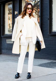 An ivory sweater is layered under an ivory suit and paired with an overcoat and black patent loafers.