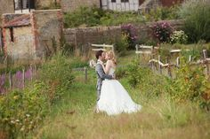 Bride and groom in the field at Grittenham Barn in summer.