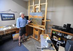 Standing in his Loveland studio, artist Russ Tanner talks Wednesday about some of his paintings and inspirations for his work. He is donating some work to
