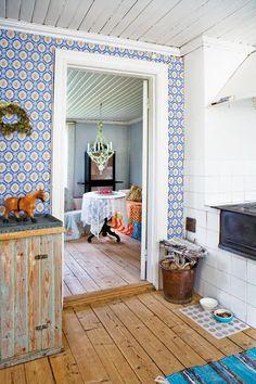 """ℰNKℰℒT, ℒANTℒIᎶT OCℋ ℳODℰℛNT: Tapeter och skurgolv fick vara kvar för att köket fortfarande skulle stämma med resten av huset. Så även det gamla skåpet i pärlspont med zinkplåt på. Eftersom tapeterna sparades stämde befintliga möbler och småprylar fortfarande väl in i stilen. Nya mattor och gardiner i bomullsvoile blev bara en fräsch komplettering. """"I stan är varmvattnet en självklarhet men här kändes det otroligt lyxigt att ha vatten, till och med varmt, i köket. Att laga mat på en bra…"""