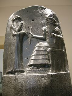 Top part of the Code of Hammurabi, ca. 1760 BCE. Hammurabi before the sun-god Shamash. Note the four-tiered, horned headdress, the rod-and-ring symbol and the mountain-range pattern beneath Shamash' feet. Black basalt.