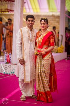 Beautiful Couple, Bride in Checkered Kanchipuram Saree with Bright Red Border and Gold Jewelry, Groom in White and Gold