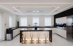 conception cuisine moderne -îlot en onyx lumineux, chaises de bar blanches, armoires en noir et blanc et éclairage indirect