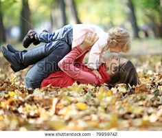 Happy family having fun in autumn park - stock photo