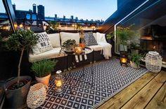 aménagement toit terrasse moderne avec un canapé en rotin et décoré d'un tapis extérieur, de coussins et de plantes vertes en pots