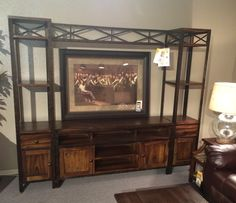 This handsome entertainment wall unit features antique iron trim and knobs.  New to our floor for only $1682.95!!!