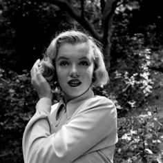Marilyn pats her curls. Naturally a brunette, Monroe reportedly dyed her hair blonde during her modeling days, after hearing that was the look agencies wanted.