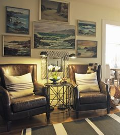 Love the art gallery wall and the following: twin leather chairs, striped RedBird-style pillows, 2 pharmacy lamps and striped rug!