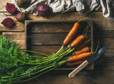 #Fresh carrots and beetroots  Healthy food cooking background. Vegetable ingredients. Fresh garden carrots and beetroots in wooden tray over rustic wooden background top view copy space horizontal composition