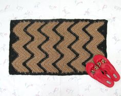 "This is a black chevron jute rug, handmade from natural jute fiber in a primitive, southwestern style. The colors are black zigzag stripes against the natural tan. This measures roughly 18"" x 31"", perfect for a kitchen, hallway, or the foot of a bed. Cats seem to love sleeping on the material, so if you're a cat person, this could be just the thing for you. Your dog would also like this as a way to get off the cold floor."