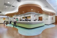 The pediatric nurses' station features aqua wood flooring and a punched-up wave shape, both of which add visual variety and fun to the area for children and their families. The orange color in the sky is inspired by the sunset and sunrise. Photo: © Jeffrey Totaro, 2014.