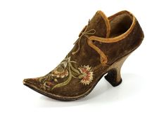 Pair of ladies shoes, probably Germany, 1730-1740. Dark brown leather, embroidered with floral motifs in polychrome silk; high heel, pointed toe.