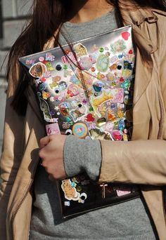 Sticker-Covered Clutch | In case you needed something to do with your childhood sticker collection. No tutorial but you can use mod podge to keep the stickers from falling off.