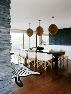 wicker pendants + rustic wood table + slip-cover chairs in beach house dining space via prue ruscoe