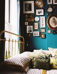 Teal wall with wood and gold frames