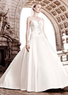 new meaning to the term show stopper.   No detail is overlooked in this gorgeous satin strapless Cassini gown featuring a bodice  Covered button detailing lends the extra touch needed for the ultimate polished look.  Dropped waist with ruching on bodice promises a beautiful silhouette.  Sizes 0-14.    Chapel train. Fully lined. Back zip. Dry clean only.  To preserve your wedding dreams, try our Wedding Gown Preservation Kit.