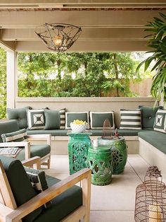 I like the grouping of tables in middle. Sage green and beige form a tranquil color palette on this patio. Modern wooden chairs are paired with wire light fixtures and ceramic garden stools to create an inviting and eclectic look. An L-shape built-in bench means everyone can come to the patio to relax.