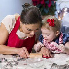 La princesse Victoria et la princesse Estelle de Suède s'appliquent, en plein atelier pâtisserie en décembre 2013 au palais Haga : un savoureux moment en famille en guise de message de voeux pour Noël.