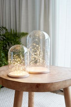 our glass dome duo is perfect for creating a peaceful and calming setting in your home. This sophisticated bundle incorporates two strings of 50 warm white micro lights, one for each dome, to bathe your interior in a soothing glow. Glass Dome Display, Glass Domes, Glass Vase, Minimalism Living, The Bell Jar, Bell Jars, Curtain Lights, Centerpieces, Table Decorations