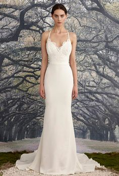 Nicole Miller. Trumpet gown with a beaded, corded scalloped lace bodice and simple waistband. Scalloped deep-V front and back neckline with scalloped lace details. Crisscross back straps and fishtail train.