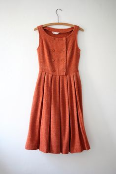 The perfect jumper dress. Wide, boat neckline. Sleeveless style perfect for layering with your favorite blouses. Double breasted button bodice. Wide box pleated full skirt. The prettiest shade of rusty orange.  Estimated size - Small  Maker - Abby Michael Ltd  Era - 1950s
