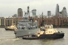 German frigate 'Niedersachsen' being turned to leave London by tugs 'Svitzer Brunel' and 'Svitzer Mercia' with Wapping and the City of London in the background