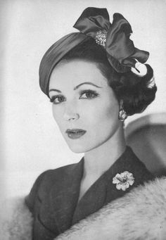 Double Brooch: on headwear and on shoulder. The modest size of both keeps it chic. 1957.