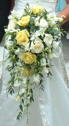 Large teardrop bouquet of soft yellow and cream roses with trailing eucalyptus…
