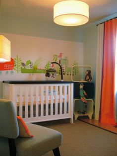 An eclectic gender  neutral nursery. The pale blue-grey with accents of orange, red and strong green  makes the space  fun and cheerful.  The square stackable shelves  and contemporary cot bed help to pull the look and feel of the room together.