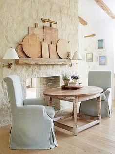 Slipcovered chairs are practical and easy to switch out for the season, and a collection of vintage cutting boards gets prime placement on an open shelf.