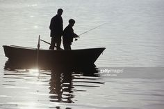Stock Photo : Silhouettes of father and son (13-14) standing in boat fishing