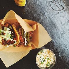 """Barrio Logan lunch vibes.  Pictured: 1 Pastor Taco (left)  1 Taco de Barrio (right)  Salud's take on a Mexican street classic: """"vasito de elote"""" aka cup of corn. Oh yeah and that ice cold Pacifico to cool down   #California #SanDiego #BarrioLogan #onthetable"""