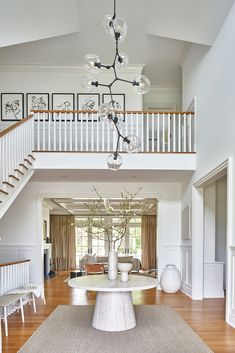 Bridgehampton — Sissy + Marley Interior Design- Dramatic and beautiful double height entryway with a round table in the foyer + modern atom chandelier + white spindles with wood railing Entryway Round Table, Entryway Stairs, Entryway Decor, Entryway Chandelier, Outdoor Chandelier, Hallway Lighting, Console Table Styling, Wood Railing, Staircase Spindles