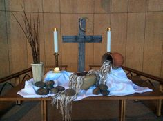 Ash Wednesday -  communion elements (wooden bowl, ceramic cup) on the left; ashes and oils for anointing in glass containers on the right; rocks and dried out palms from last year at the bottom of the altar.
