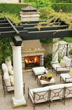 Lovely courtyard with conversation area and fireplace under pergola...