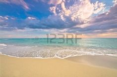 Idyllic empty beach panorama with turquoise ocean surf and delicate sunset…