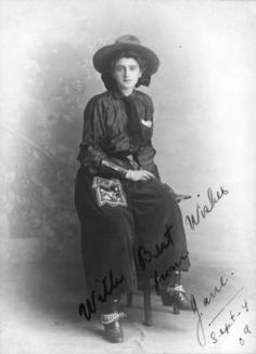 Studio portrait of Jane Bernoudy, an actress and trick roper born in New Castle, Colorado. She wears cowgirl clothes, spurs, boots, an embroidered pouch, leather gauntlets, and a cowboy hat (Sept 4, 1909).