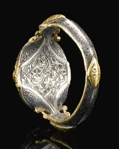 A FINE AND RARE SELJUK SILVER AND GOLD RING SET WITH A DEEP PURPLE STONE SEAL BEARING THE NAME OF ALI IBN YUSUF, PERSIA, 12TH CENTURY.