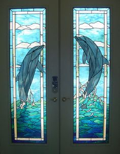 Playful dolphin double door by ambient stained glass.