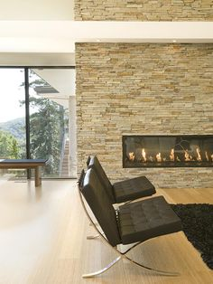 A long, rectangular design is a trending style for gas fireplaces. Extending this stone fireplace to the ceiling adds to its contemporary aesthetic.