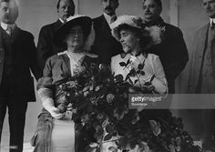 American teacher Anne Sullivan Macy (1866 - 1936) (left) and her former student, author and activist Helen Keller (1880 - 1968) sit together while several dignitaries stand behind them at the International Flower Show, New York, New York,April 8, 1913. They visited the show during their lecture tour of the Northeastern United States.