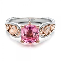 #100570 This exquisite engagement ring features a cushion shaped pink sapphire prong set in rose gold, accented with diamonds, filigree, and custom hand engraving on the...