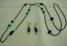 """Downton Abbey necklace and earrings. Inspired by the elegant jewelry on """"Downton Abbey"""", this long necklace is made with coated black chain, faceted crystals, shaped onyx beads, and bright green stone beads. The matching earrings are on gold-plated ear wires. Donated by Jackie Spafford."""